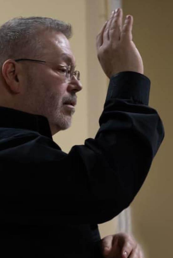 John Bradley raising hand directing choir