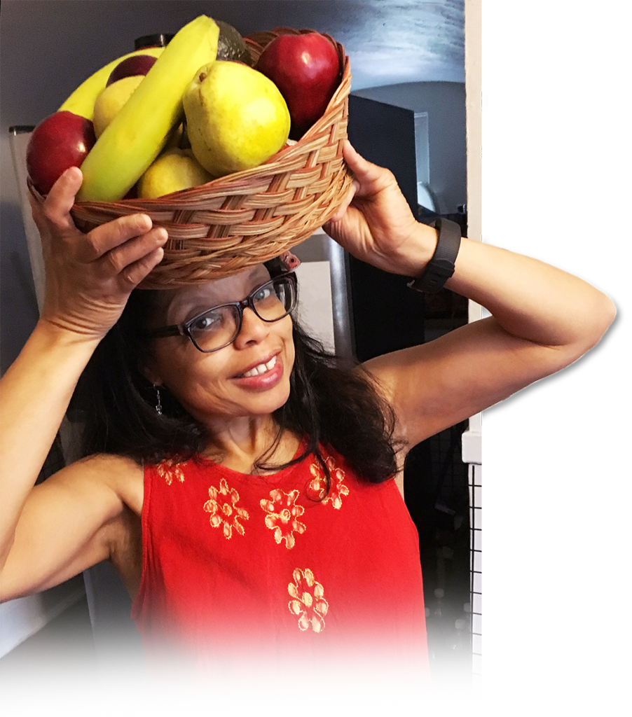 Addell Anderson holding a basket of fruit on her head