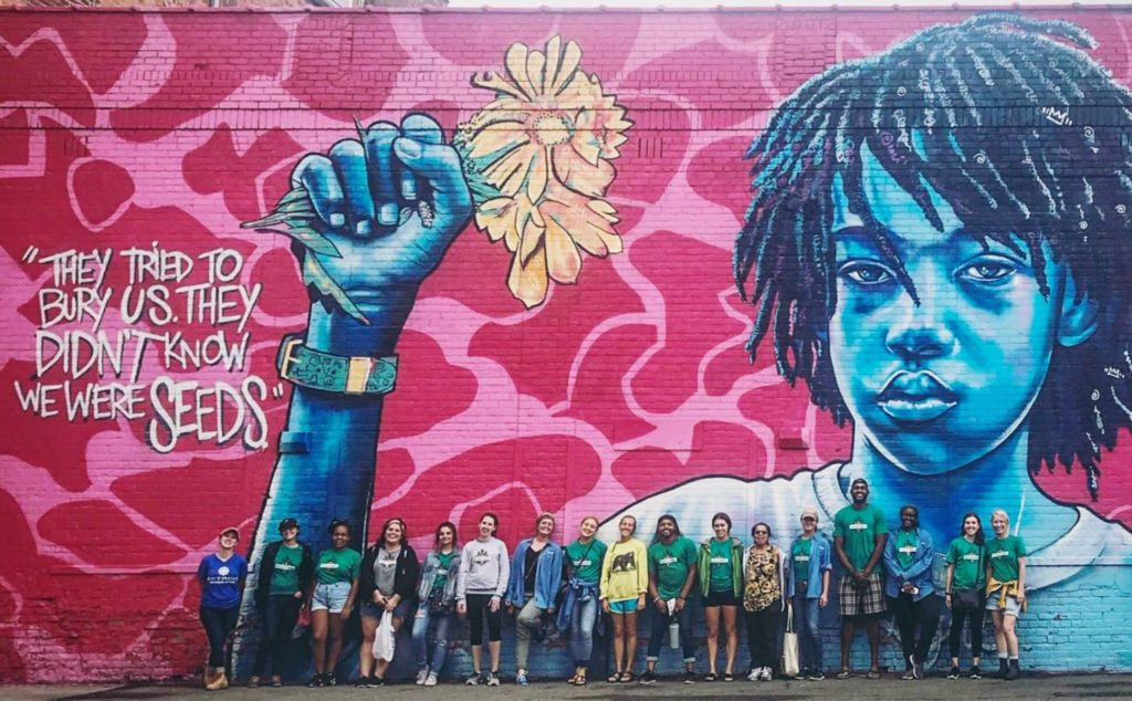 """FoodCorps members standing in fronton a building with a huge painting n the side and the caption: """"They tried to bury us. They didn't know we were seeds."""""""