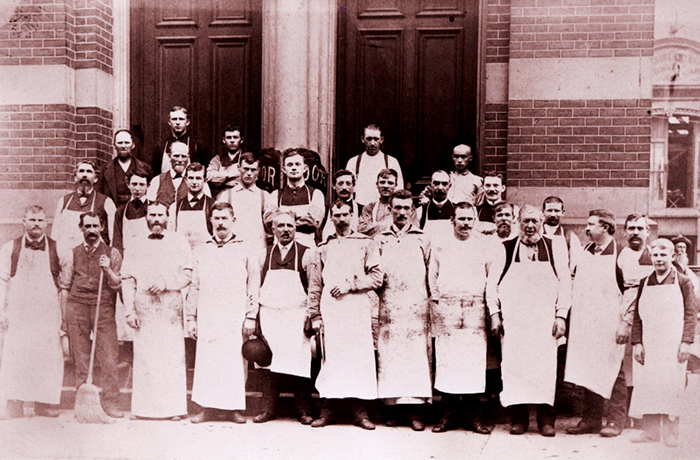 Historical photo of a group of employees standing out front of building