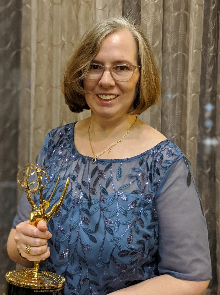 Katy Loebrich holding Emmy trophy
