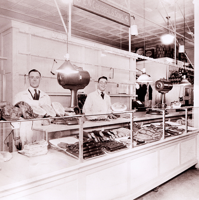 Historical photo of two butches behind meat counter