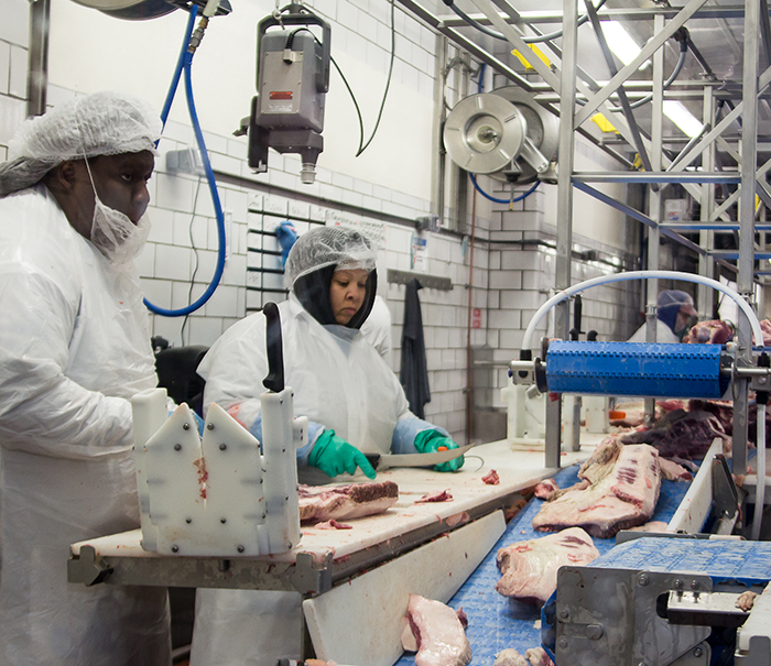 Workers trimming meat in the plant
