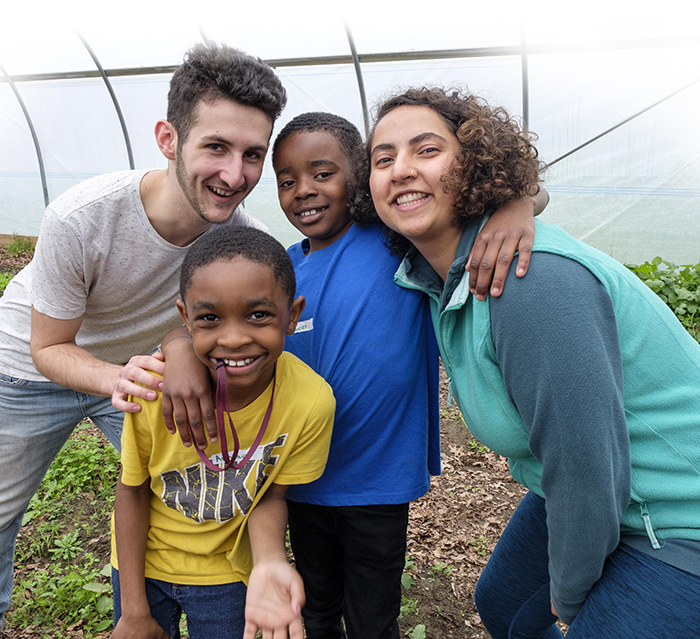two Kalamazoo College students posing with two Woodward elementary school students in the Hoop House