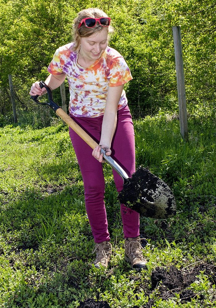 Student digging dirt with a shovel