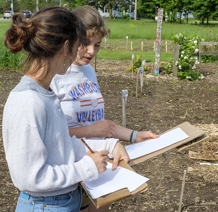 Two students drawing layouts of the garden they are standing at