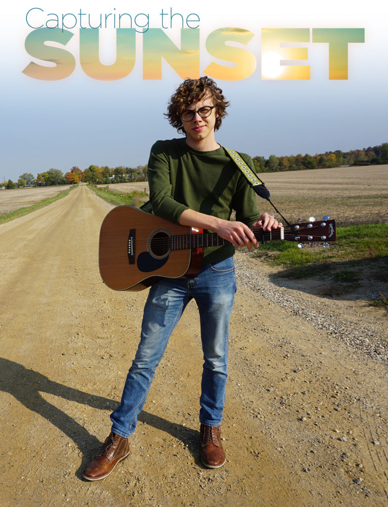 Jonathan Townley standing on dirt road with guitar